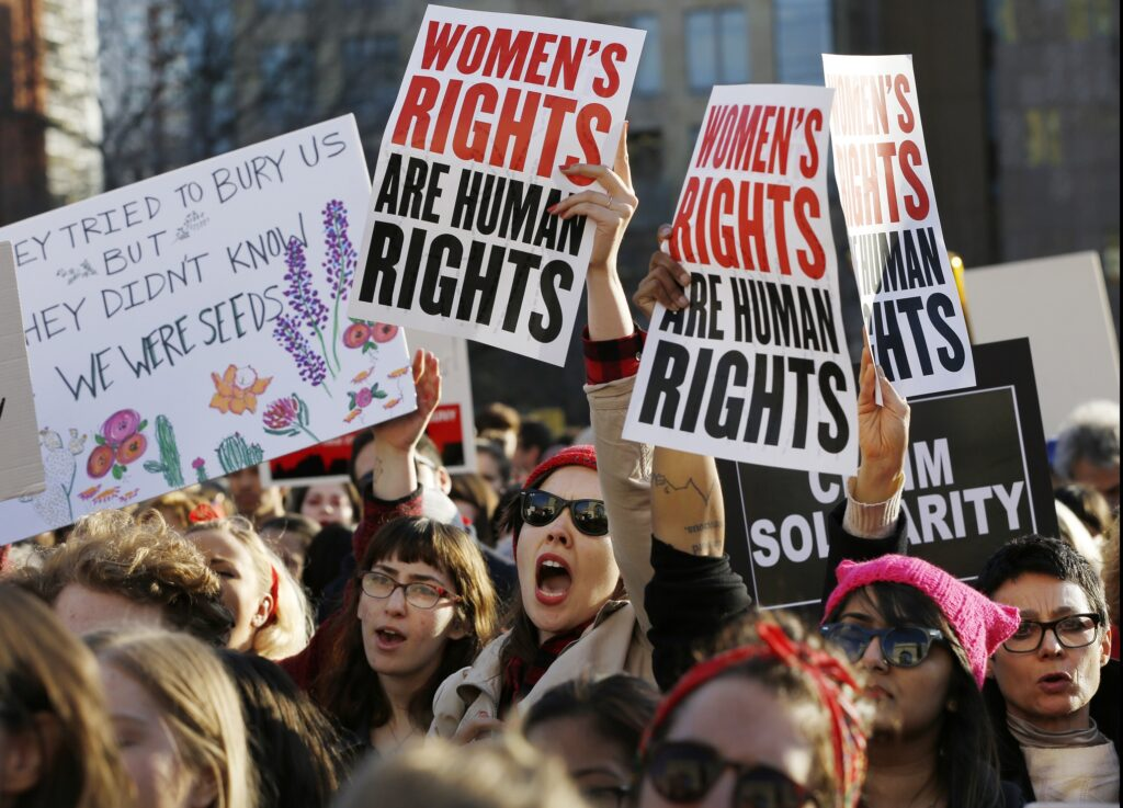Women chant and hold signs during a rally