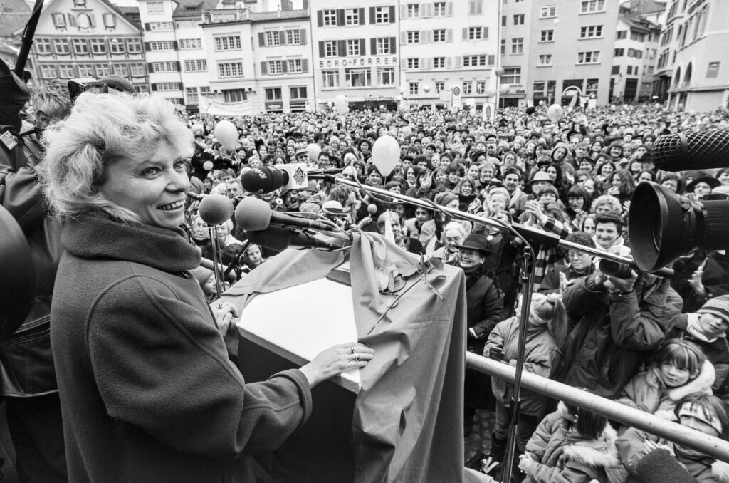 Photo black and white of Christiane Brunner, in front of a microphone, facing a huge crowd